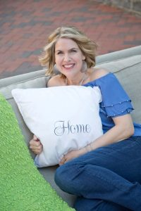 Jan Copeland sitting on couch with home pillow
